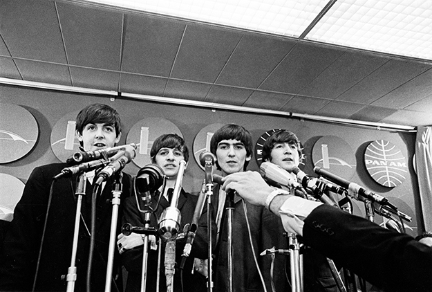 (L-R) Paul McCartney, Ringo Starr, George Harrison and John Lennon arrive to face a phanlanx of reporters at JFK airport on February 7, 1964.