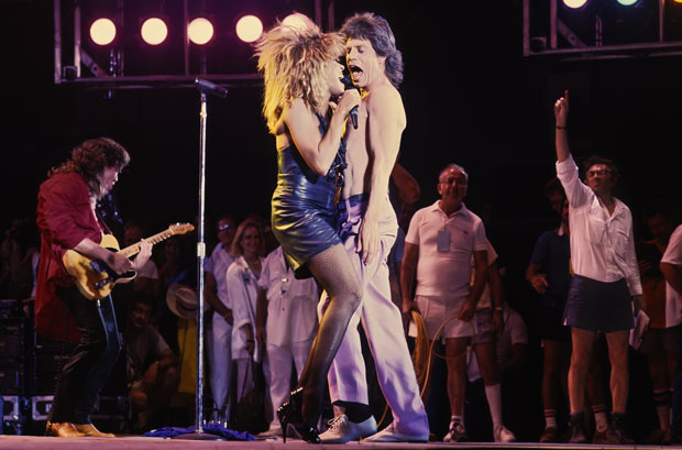 Graham motions from backstage as Tina Turner and Mick Jagger perform at Live Aid, 1985. © Lynn Goldsmith.