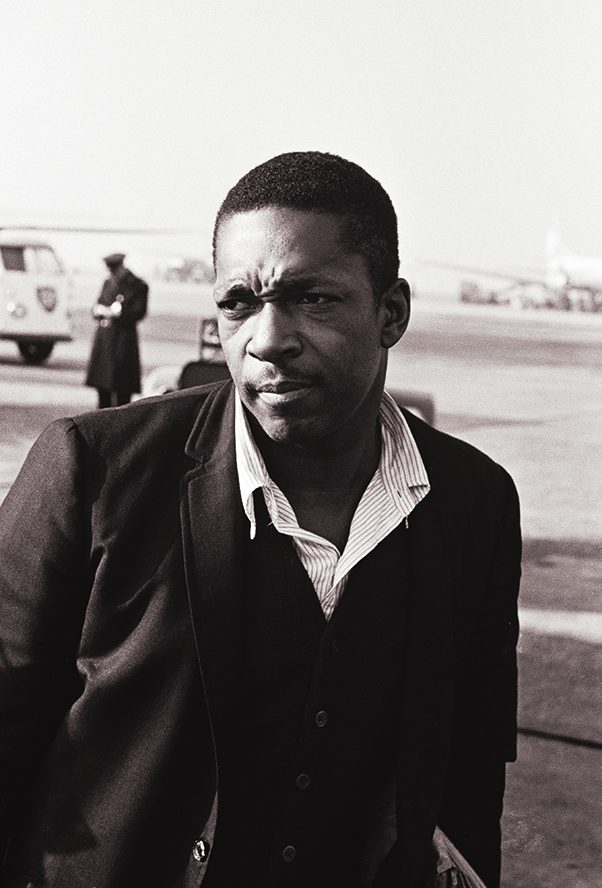 Jazz saxophonist, John Coltrane arriving at Schiphol Airport, Amsterdam, Netherlands, 1963.  Wikimedia Commons | Dutch Natonal Archives